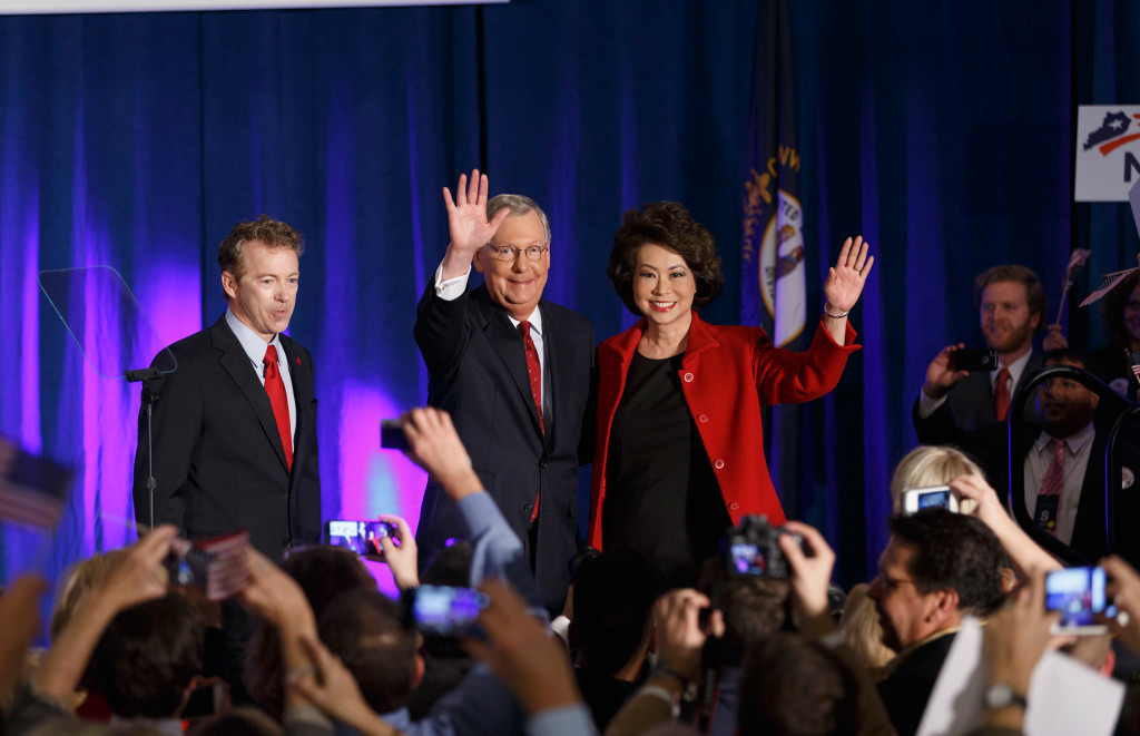Senate Minority Leader Mitch McConnell of Ky., center, celebrates with Sen. Rand Paul, R-Ky., left, and his wife, former Labor Secretary Elaine Chao, at an election night party in Louisville, Ky.,Tuesday, Nov. 4, 2014. McConnell won a sixth term in Washington, with his eyes on the larger prize of GOP control of the Senate. The Kentucky Senate race, with McConnell, a 30-year incumbent fighting off a spirited challenge from Democrat Alison Lundergan Grimes, has been among the most combative and closely watched contests that could determine the balance of power in Congress. (AP Photo/J. Scott Applewhite)